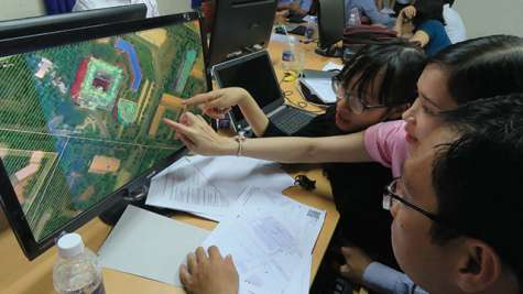 People looking at a satellite image on a computer screen and pointing out various buildings